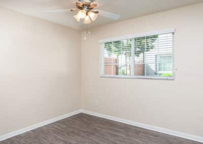 empty-bedroom-with-ceiling-fan-and-window